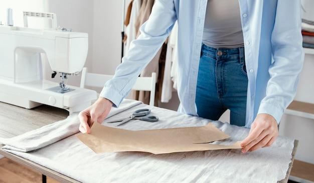 Vooraanzicht van vrouwelijke kleermaker stof voorbereiden op kleding Gratis Foto
