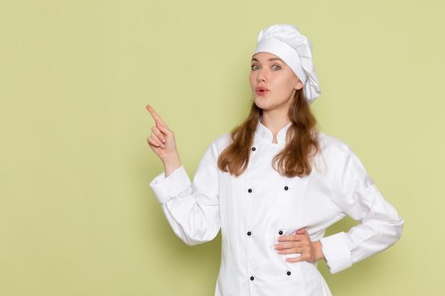 Vooraanzicht van vrouwelijke kok in het witte kokkostuum stellen op de groene muur Gratis Foto