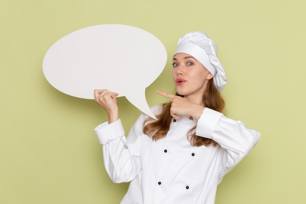 Vooraanzicht van vrouwelijke kok in wit kokkostuum die wit teken op de groene muur houden Gratis Foto