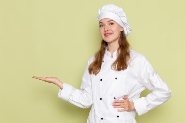 Vooraanzicht van vrouwelijke kok in wit kokkostuum het glimlachen stellen op groene muur Gratis Foto