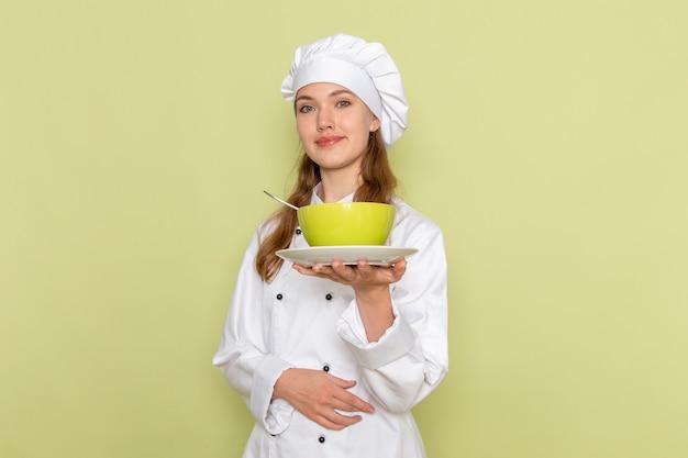 Vooraanzicht van vrouwelijke kok in witte kokkostuum die groene plaat op de groene muur glimlachen Gratis Foto
