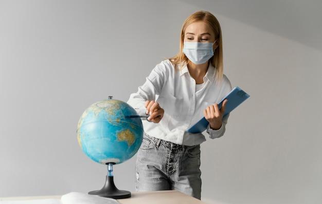 Vooraanzicht van vrouwelijke leraar in klaslokaal met klembord die naar bol wijst Gratis Foto