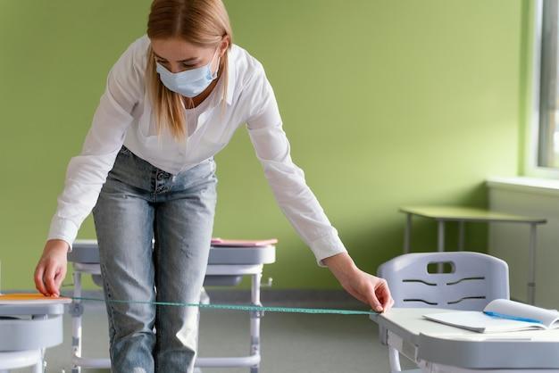 Vooraanzicht van vrouwelijke leraar met medisch masker die afstand tussen klassenbanken meten Gratis Foto