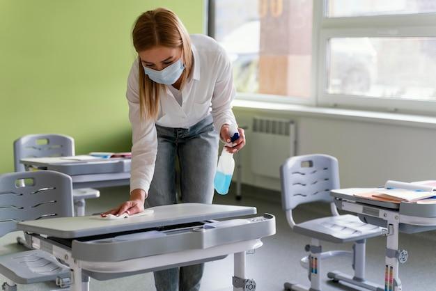 Vooraanzicht van vrouwelijke leraar schoolbanken in de klas desinfecteren Gratis Foto