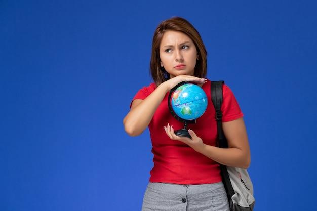 Vooraanzicht van vrouwelijke student in rood overhemd met rugzak die kleine bol op de blauwe muur houdt Gratis Foto
