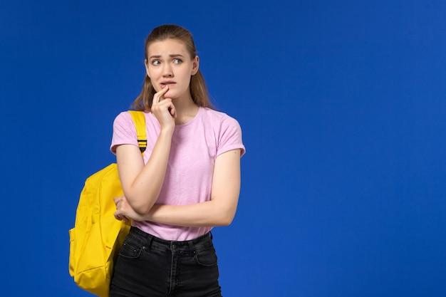 Vooraanzicht van vrouwelijke student in roze t-shirt met gele rugzak die op de blauwe muur denken Gratis Foto
