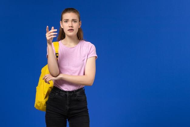 Vooraanzicht van vrouwelijke student in roze t-shirt met gele rugzak op de blauwe muur Gratis Foto