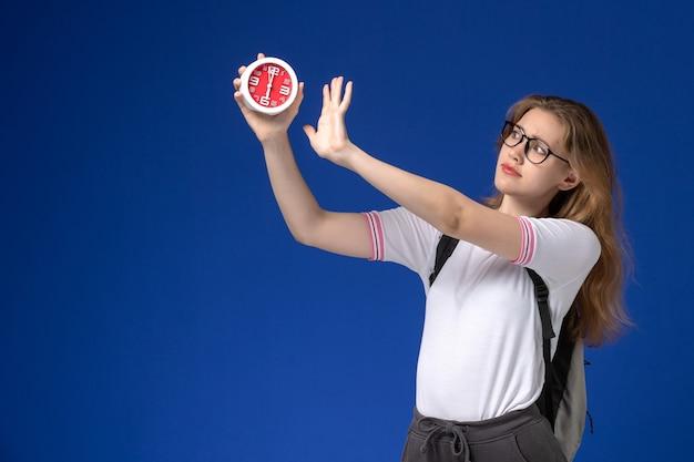 Vooraanzicht van vrouwelijke student in wit overhemd die de klokken van de rugzakholding op blauwe muur dragen Gratis Foto