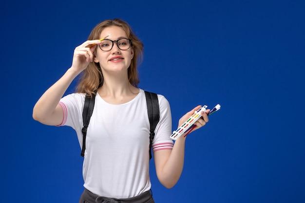 Vooraanzicht van vrouwelijke student in wit overhemd die rugzak dragen en kunstverfborstel op blauwe muur houden Gratis Foto