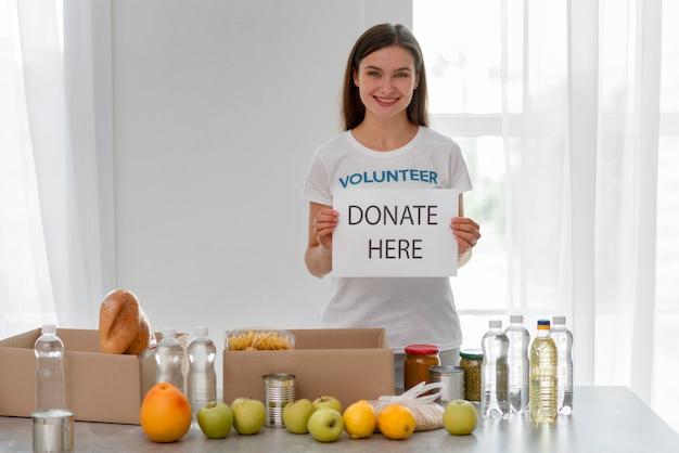 Vooraanzicht van vrouwelijke vrijwilliger die voedselschenkingen voorbereidt Gratis Foto
