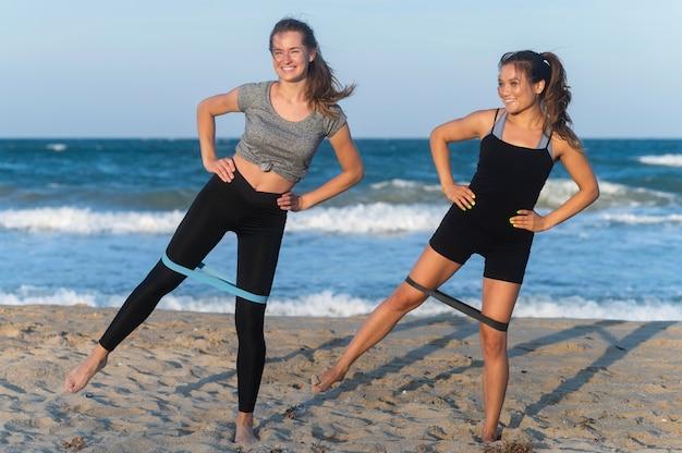 Vooraanzicht van vrouwen die op het strand uitoefenen Gratis Foto