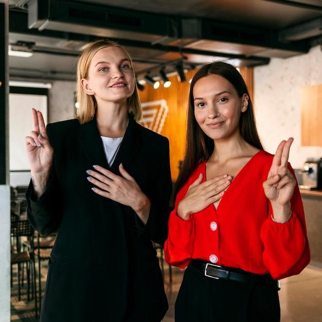 Vooraanzicht van vrouwen op het werk die gebarentaal gebruiken om te communiceren Gratis Foto