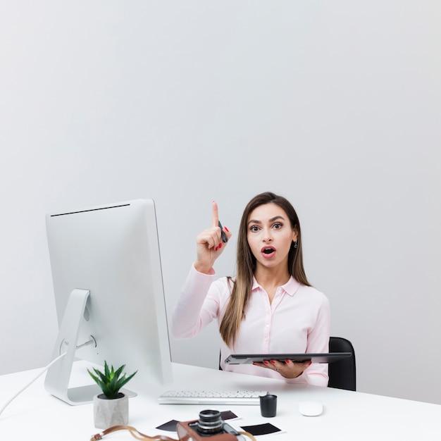 Vooraanzicht van vrouwenzitting bij bureau en het hebben van een idee Gratis Foto