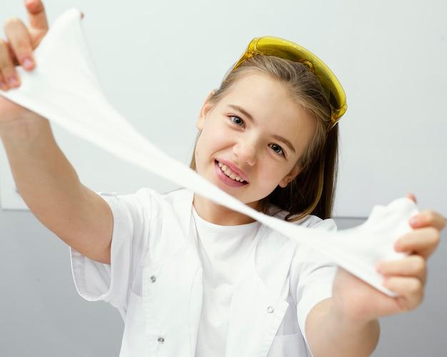 Vooraanzicht van wetenschapper die van het smiley jonge meisje met slijm experimenteert Premium Foto