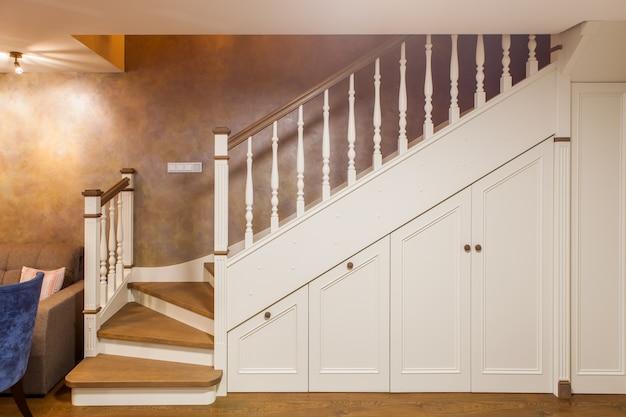 Vooraanzicht van witte trap naar de tweede verdieping met ingebouwde kluisjes van hout. klassiek interieur van een gastenkamer in een appartement met twee verdiepingen. Premium Foto