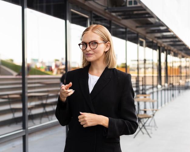 Vooraanzicht van zakenvrouw met gebarentaal buitenshuis op het werk Gratis Foto