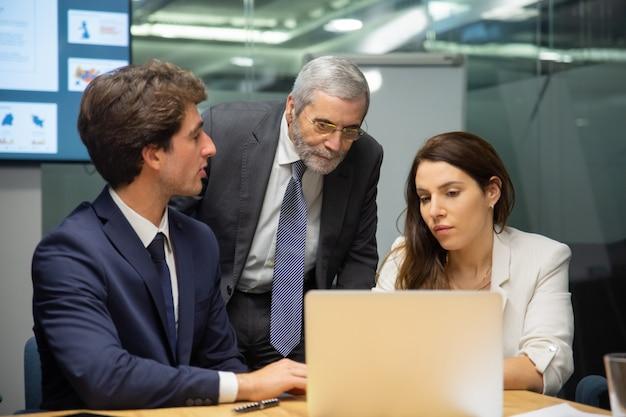 Vooraanzicht van zeker commercieel team dat laptop bekijkt Gratis Foto