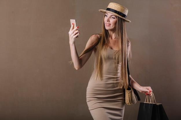 Vooraanzicht verbluffende vrouw die haar telefoon controleert Gratis Foto