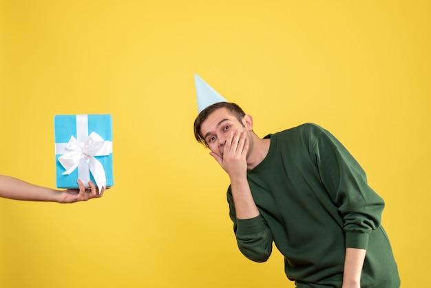 Vooraanzicht verrast jongeman cadeau in menselijke hand op geel Gratis Foto