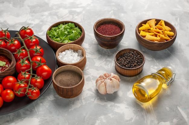 Vooraanzicht verse cherrytomaatjes binnen plaat met verschillende kruiden op witte oppervlakte plantaardige maaltijd voedsel gezondheid salade Gratis Foto