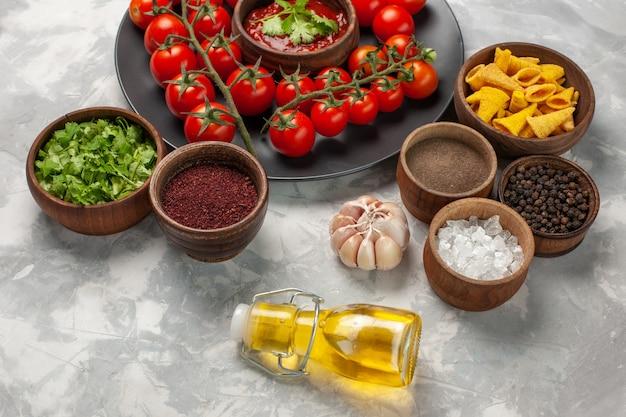 Vooraanzicht verse kersentomaten binnen plaat met greens en verschillende kruiden op witte het voedselgezondheidssalade van de oppervlakte plantaardige maaltijd Gratis Foto