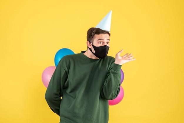 Vooraanzicht verwarde jonge man met feestmuts en kleurrijke ballonnen staande op geel Gratis Foto