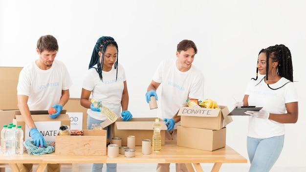 Vooraanzicht vrijwilligers die zorgen voor donaties Gratis Foto