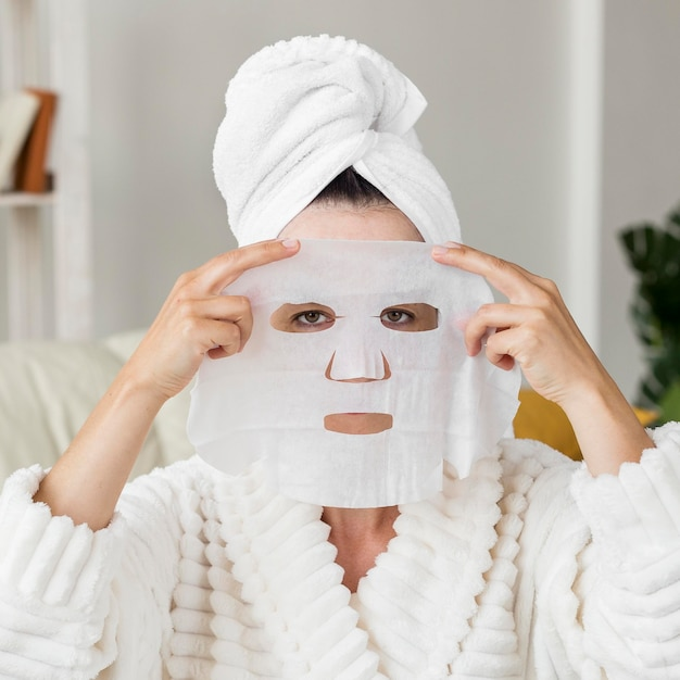 Vooraanzicht vrouw gezichtsmasker toe te passen Gratis Foto