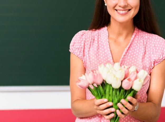 Vooraanzicht vrouw met een boeket bloemen van haar studenten Gratis Foto
