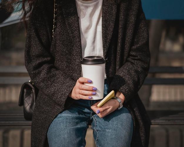 Vooraanzicht vrouw met een kopje koffie en wachtend op de bus Gratis Foto