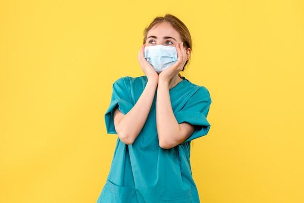 Vooraanzicht vrouwelijke arts opgewonden op gele achtergrond ziekenhuis gezondheid covid-pandemie Gratis Foto