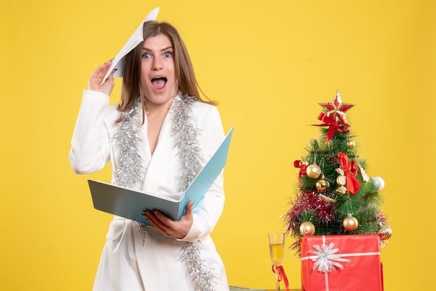 Vooraanzicht vrouwelijke arts permanent en houdt documenten op gele achtergrond met kerstboom en geschenkdozen Gratis Foto