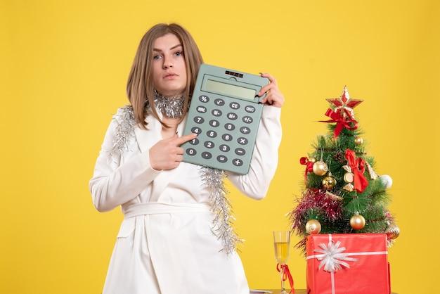 Vooraanzicht vrouwelijke arts permanent en houdt rekenmachine op gele achtergrond met kerstboom en geschenkdozen Gratis Foto