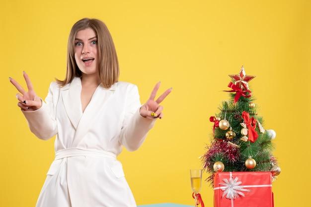 Vooraanzicht vrouwelijke arts staande rond tafel met kleine kerstboom op de gele achtergrond Gratis Foto