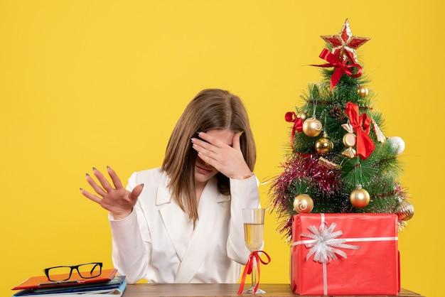 Vooraanzicht vrouwelijke arts zit achter haar tafel benadrukt op gele achtergrond met kerstboom en geschenkdozen Gratis Foto