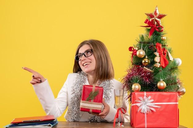 Vooraanzicht vrouwelijke arts zit tafel met cadeautjes en boom op gele achtergrond met kerstboom en geschenkdozen Gratis Foto
