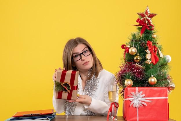 Vooraanzicht vrouwelijke arts zit voor haar tafel bedrijf aanwezig op gele achtergrond met kerstboom en geschenkdozen Gratis Foto