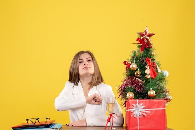Vooraanzicht vrouwelijke arts zit voor haar tafel op gele achtergrond met kerstboom en geschenkdozen Gratis Foto