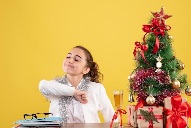 Vooraanzicht vrouwelijke arts zittend achter tafel met kerstcadeautjes en boom op gele achtergrond Gratis Foto