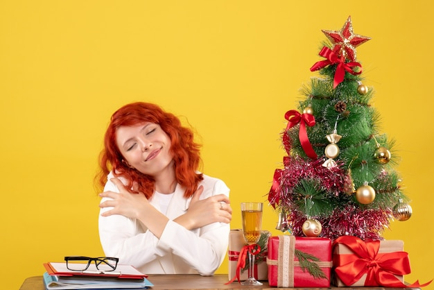 Vooraanzicht vrouwelijke arts zittend achter tafel met kerstcadeautjes op gele achtergrond met kerstboom en geschenkdozen Gratis Foto