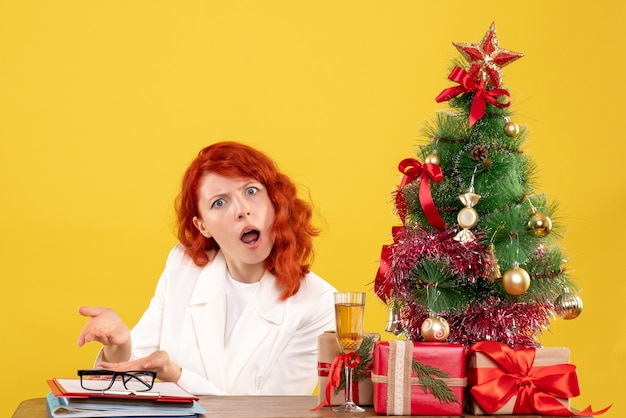 Vooraanzicht vrouwelijke arts zittend achter tafel met kerstcadeautjes op gele achtergrond Gratis Foto