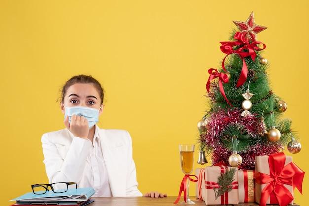 Vooraanzicht vrouwelijke arts zittend in beschermend masker op gele achtergrond met kerstboom en geschenkdozen Gratis Foto