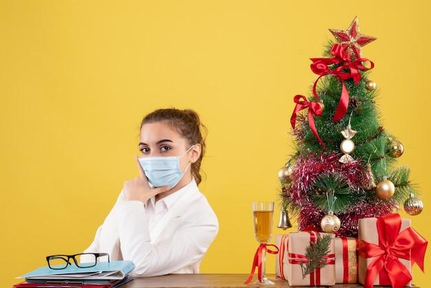Vooraanzicht vrouwelijke arts zittend in steriel masker op gele achtergrond met kerstboom en geschenkdozen Gratis Foto