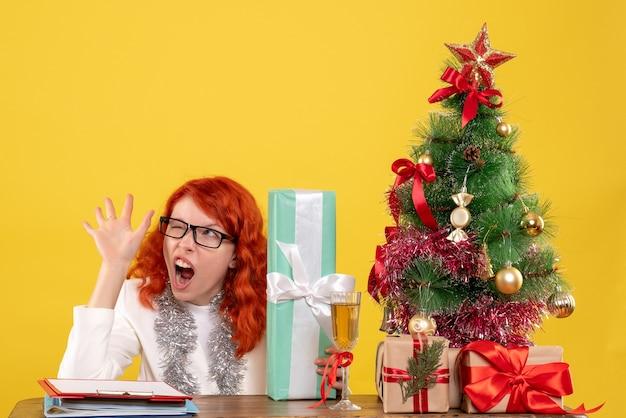 Vooraanzicht vrouwelijke arts zittend met kerstcadeautjes en boom op gele achtergrond Gratis Foto