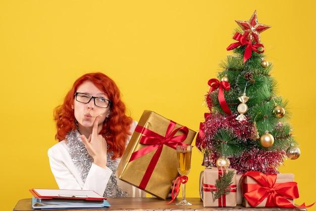 Vooraanzicht vrouwelijke arts zittend met kerstcadeautjes op gele achtergrond Gratis Foto