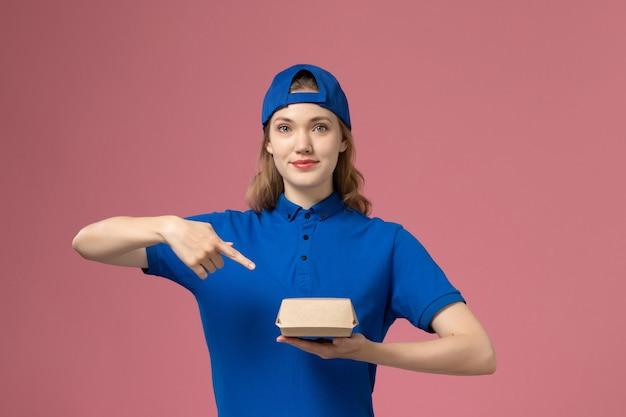 Vooraanzicht vrouwelijke koerier in blauw uniform en cape die weinig voedselpakket op de roze achtergrond houden Gratis Foto