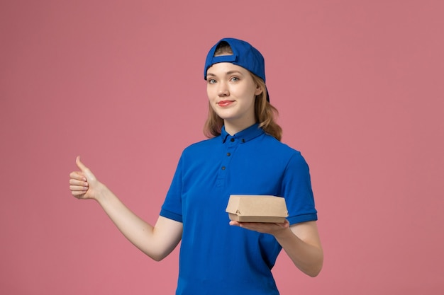 Vooraanzicht vrouwelijke koerier in blauw uniform en cape met weinig bezorgvoedselpakket op de roze achtergrond levering uniform servicebedrijf werkbaan Gratis Foto
