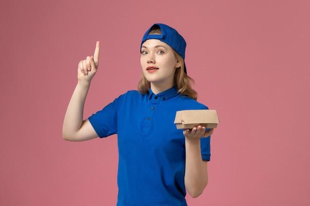 Vooraanzicht vrouwelijke koerier in blauw uniform en cape met weinig bezorgvoedselpakket op roze achtergrond baanbezorging uniform servicewerkbedrijf Gratis Foto