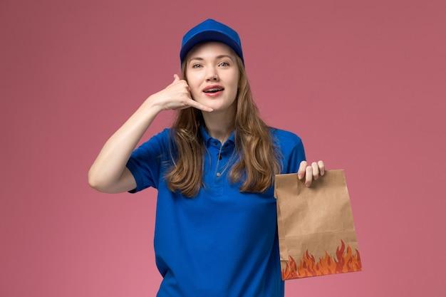 Vooraanzicht vrouwelijke koerier in blauw uniform houden voedselpakket telefoongesprek gebaar op roze bureau baan werknemer dienst uniform bedrijf tonen Gratis Foto