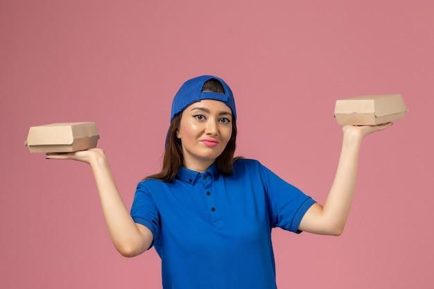 Vooraanzicht vrouwelijke koerier in blauwe uniforme cape met kleine afleverpakketten op roze muur, werknemer dienstverleningswerk meisje Gratis Foto